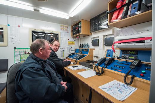 die Feuerwehrleute Michael Geiling, im Hintergrund Rainer Weise – im Führungskraftwagen